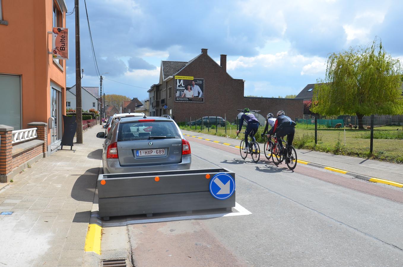 De nieuwe geschrankte parkeerplaatsen met (lege) bloembakken in de Schoolstraat in Denderhoutem.