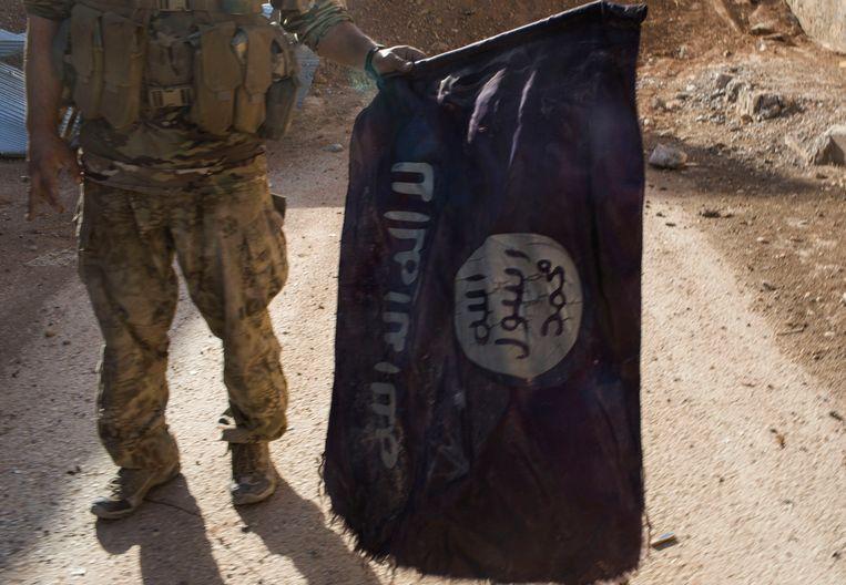 Een SDF-strijder met een vlag van IS, archiefbeeld. Beeld Photo News