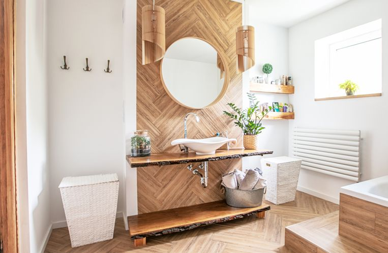 White sink on wood counter with a round mirror hanging above it. Bathroom interior. Beeld Getty Images/iStockphoto