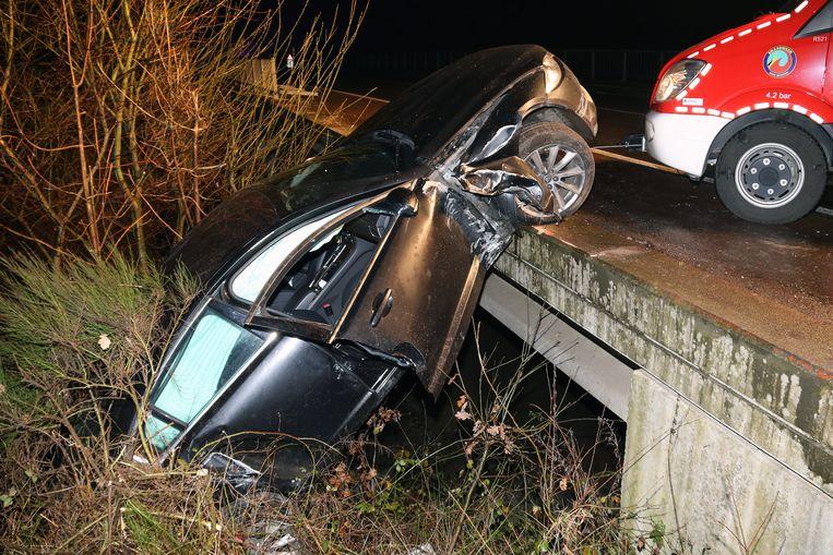 De Jaguar gleed van de brug, maar bleef nog met de voorwielen aan een boordsteen hangen.
