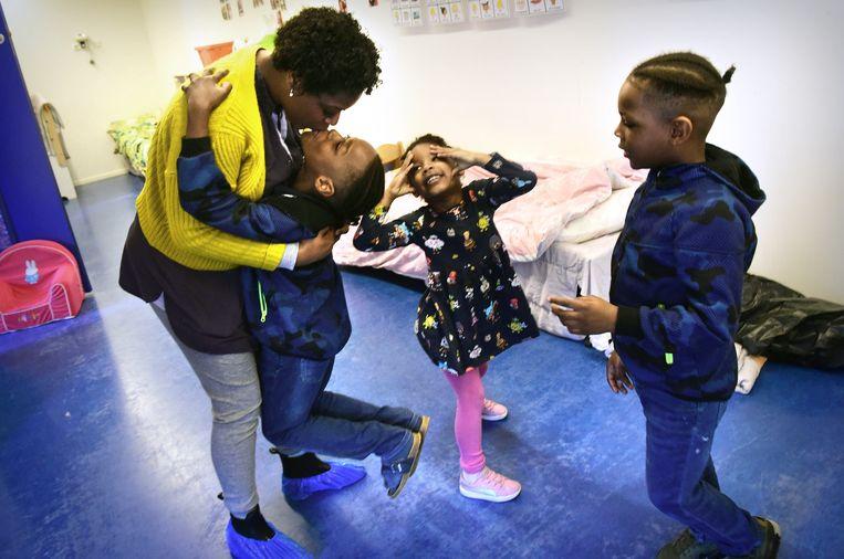 Zorgmedewerker Jurynaidy Reenis neemt afscheid van haar kinderen in de 24-uursopvang naast het Rotterdamse Maasstadziekenhuis. Beeld Marcel van den Bergh / de Volkskrant