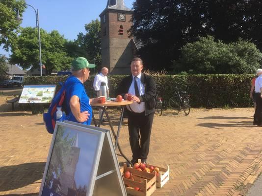 Dominee Arie Simons deelt in Valburg appels uit aan Vierdaagselopers.
