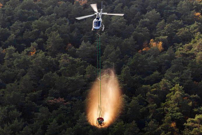 Met een helikopter wordt er kalksteen over de Veluwe uitgestrooid.