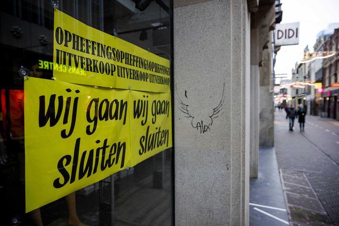 Op het raam van een gesloten winkel hangt een bord met de tekst wij gaan sluiten