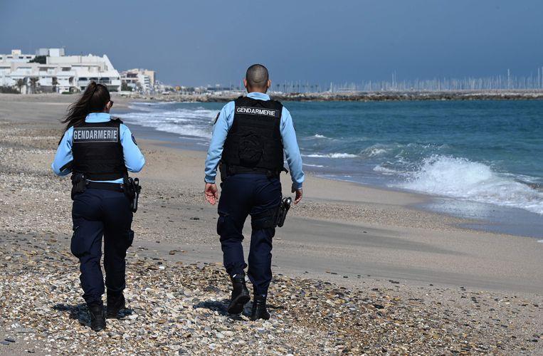 Franse agenten op het verlaten strand van het Zuid-Franse Palavas les Flots, nabij Montpellier. Vanwege het coronavirus blijven veel Franse stranden mogelijk nog lang verboden gebied voor buitenlandse toeristen. Beeld AFP