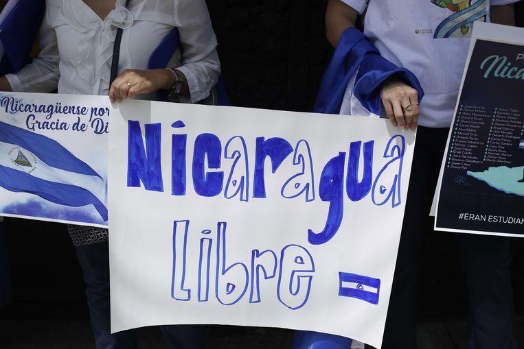 Demonstranten houden een bordje vast met daarop 'Nicaragua vrij'. Beeld EPA