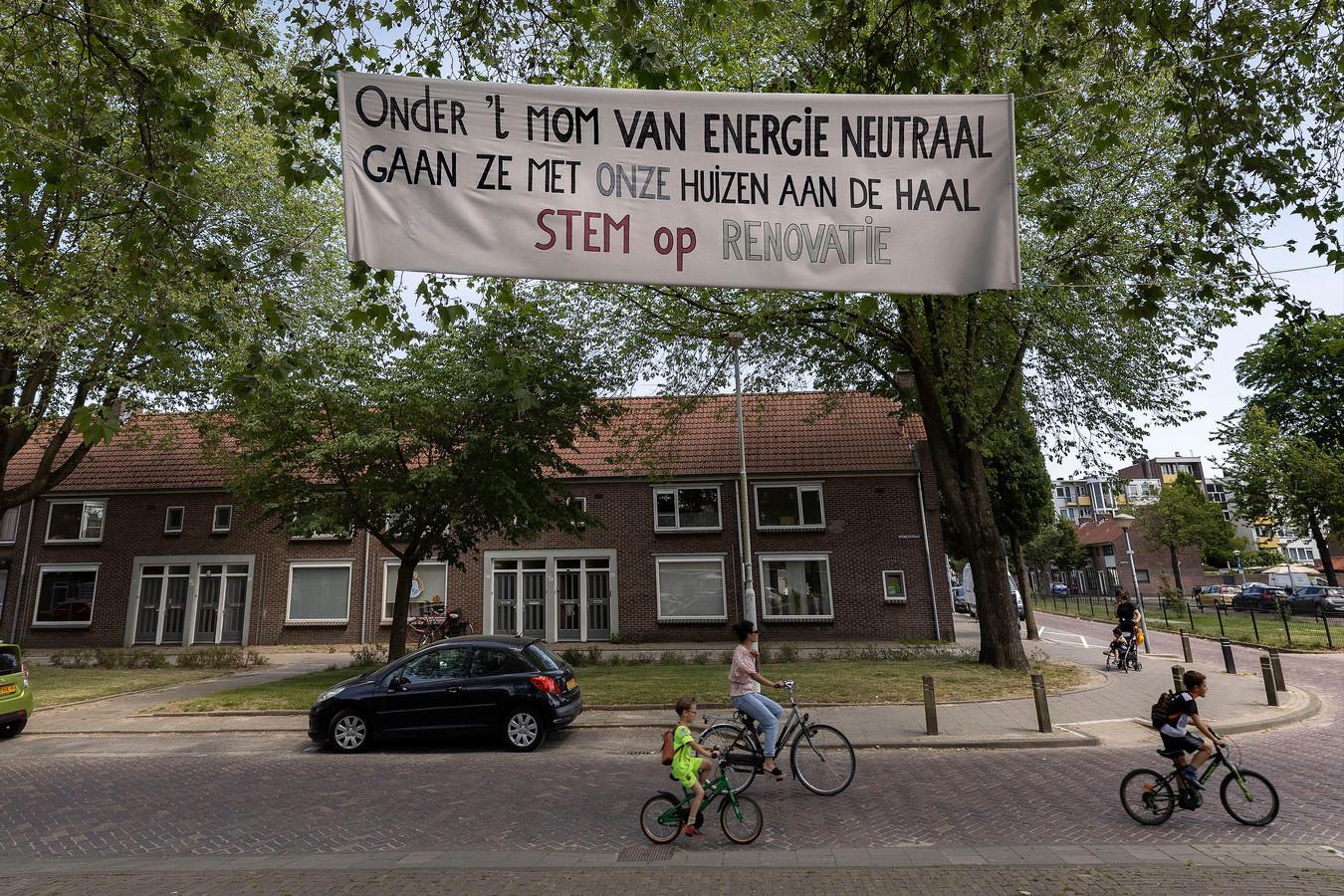 In de Gildebuurt in Eindhoven moeten bewoners kiezen tussen renoveren en sloop nieuwbouw. Dit spandoek tussen bomen op pleintje Bakkerstraat/Verwerstraat pleit voor renovatie.