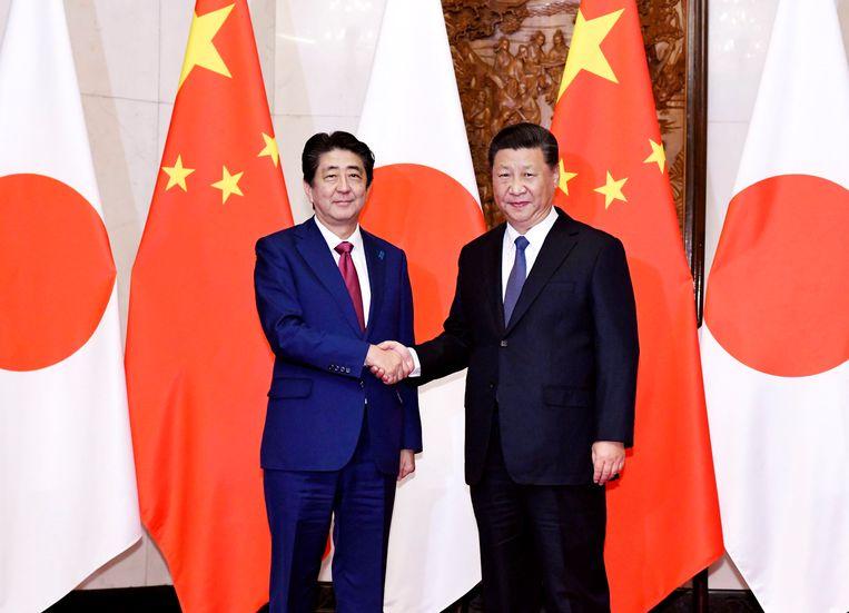 De Japanse premier Shinzo Abe (links) met de Chinese president Xi Jinping in Peking op vrijdag.  Beeld AP