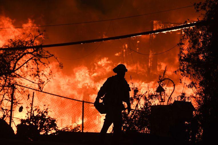 Een brandweerman in actie bij een bosbrand in 2018 in de omgeving van Malibu.  Beeld AFP