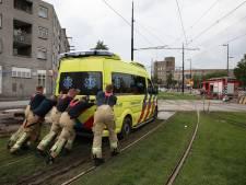 Brandweermannen duwen ambulance uit de modder