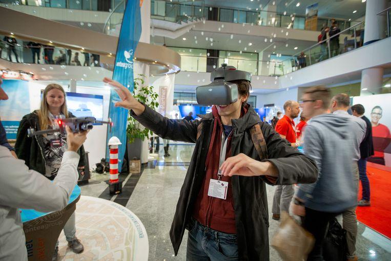 In de Expo bij het hotel WestCord WTC presenteren technische bedrijven zich aan studenten, zoals Antea. Een jongen met een virtuele bril kan zien wat met de drone wordt opgenomen.  Beeld Herman Engbers