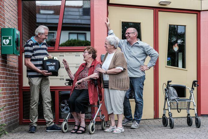 Jos Gerritzen laat trots de nieuwe aed zien aan de bewoners Mieke (links) en Dora van seniorencomplex Lobede. Alfred Sommers kijkt ondertussen tevreden toe.