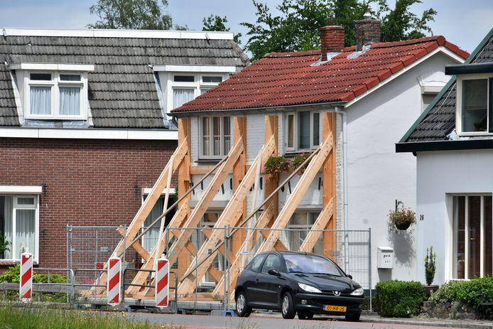 In Daarlerveen houden zware balken de gevel van een huis overeind.