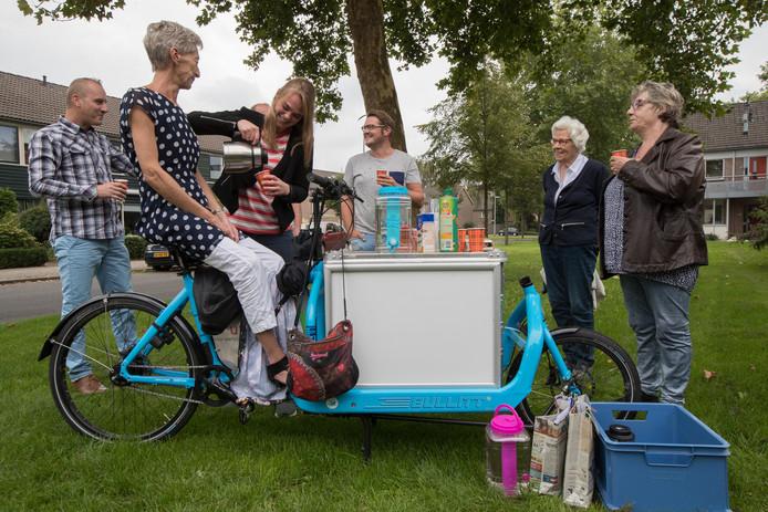 Marijke Geerligs schenkt koffie in voor de bezoekers bij de bakfiets van de Wijksafari in de Kortricklaan in Olst. Daar komt de golfslag van gesprekken tussen buurtbewoners op gang.