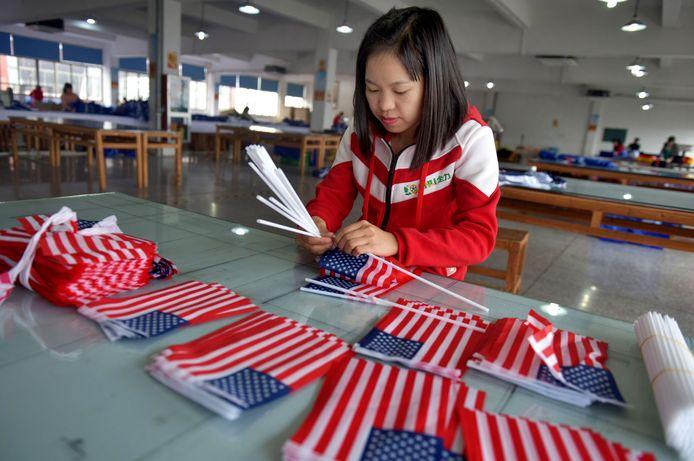Een Chinese medewerkster van een textielfabriek plakt Amerikaanse vlaggetjes aan elkaar.  Foto Stringer