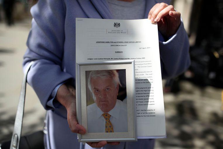 De weduwe van postmaster Julian Wilson – hij overleed in 2016 – toont bij het gerechtshof in Londen een foto van haar man. Zijn eerdere, naar nu blijkt onterechte veroordeling, werd vrijdag door het hof nietig verklaard.  Beeld AP