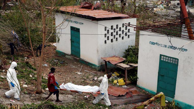 Reddingswerkers dragen een lichaam weg van een orkaanslachtoffer in Haïti. Beeld REUTERS