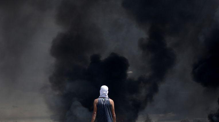 Een Palestijnse demonstrant staat voor een muur van rook tijdens een protest. Beeld EPA