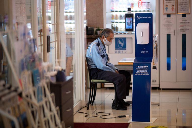 Een beveiliger in een hotel in de Olympische gaststad Tokyo controleert scherp op de naleving van de coronamaatregelen.  Beeld AFP
