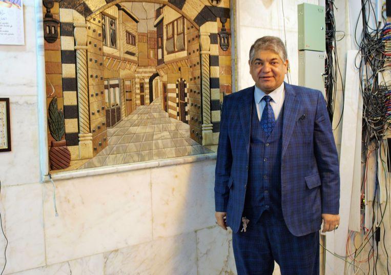 Hoteleigenaar Badr al-Jilawi voor een schilderij van oud-Damscus dat in zijn kantoor in Najaf hangt Beeld Judit Neurink