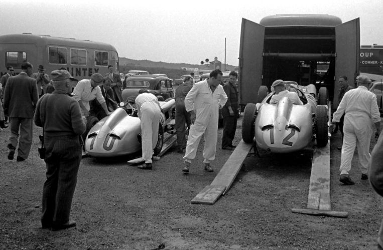 De Daimler Benz AG Mercedes W196-raceauto's van Stirling Moss (nr. 10) en Karl Kling (nr. 12) worden uitgeladen voor de Grand Prix in juni 1955. Beeld Getty