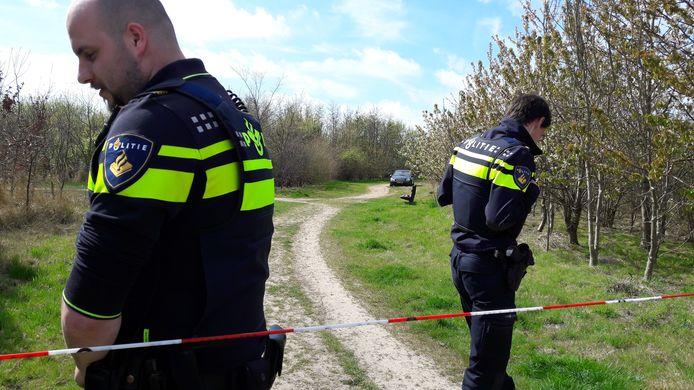 Politie-agenten staan vlakbij de plek waar de man en vrouw dood werden gevonden. In de verte de Mercedes die werd aangetroffen.