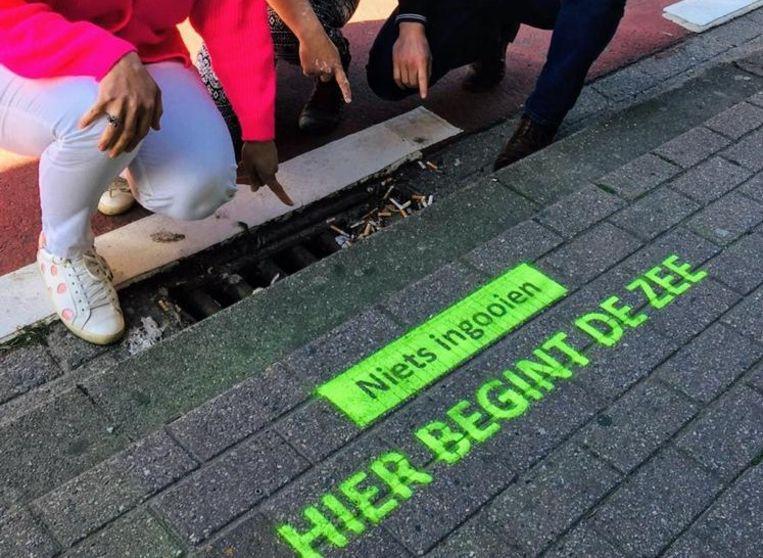 Aan het rioolrooster aan het Gemeenteplein werd de eerste sensibiliserende slogan aangebracht.