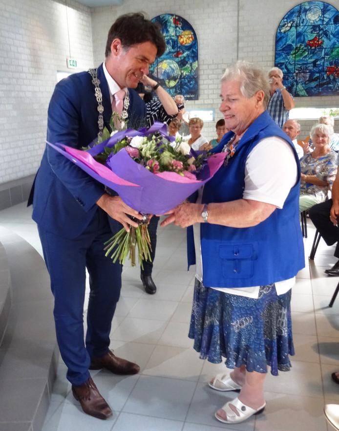 Burgemeester Depla overhandigt Joke Hermans-Verwijmeren een bloemetje.