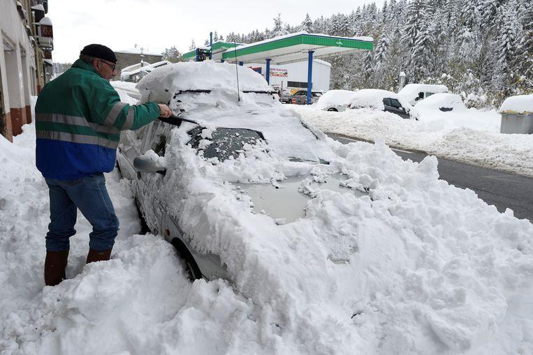 Een man verwijdert sneeuw van zijn wagen in Firminy in de Haute Loire. Beeld AFP