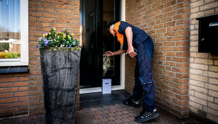 Jos brengt pakketjes rond in Duiven. Beeld Freek van den Bergh / de Volkskrant