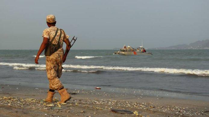 Een militair op het strand bij de havenstad Aden in Jemen.