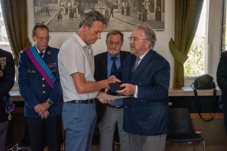 Herman De Croo schenkt postuum gouden medaille Carnegie Hero Fund aan de ouders van David Verhelst en knuffelt de vader innig.