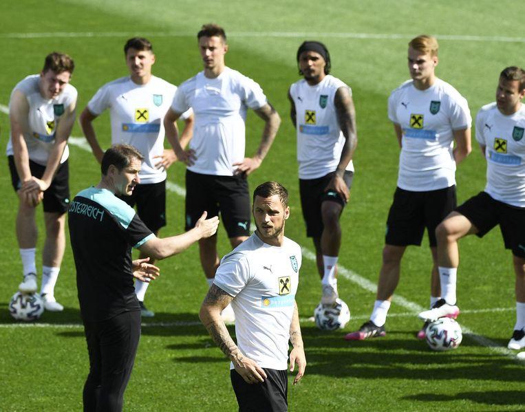 'Enfant terrible' Marko Arnautovic is afgeleid terwijl de Duitse bondscoach Franko Foda de rest van de Oostenrijkse selectie toespreekt tijdens een training op het basiskamp in Seefeld.  Beeld AFP