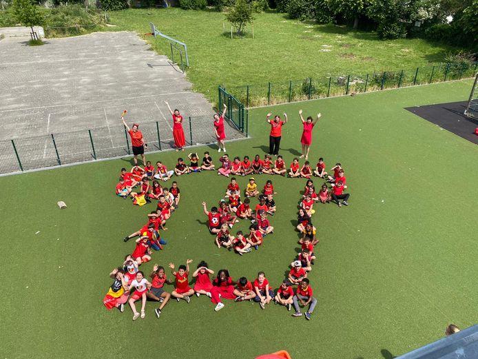 In basisschool De Knipoog maakte elke klas een figuur op de speelplaats. Deze leerlingen vormen samen een voetbalshirt.