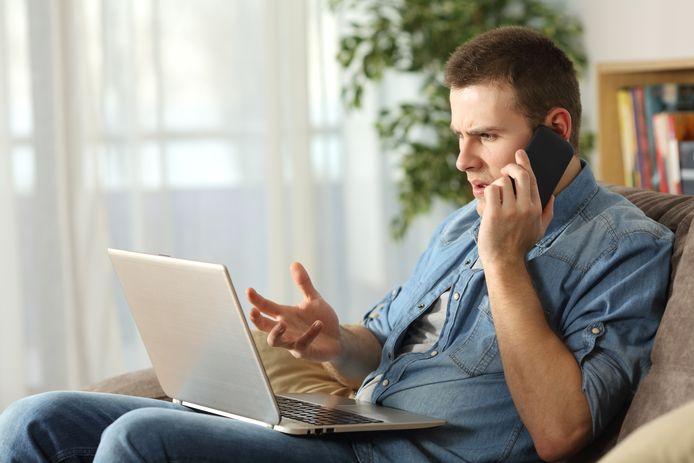 Gestresste man op laptop en mobiel