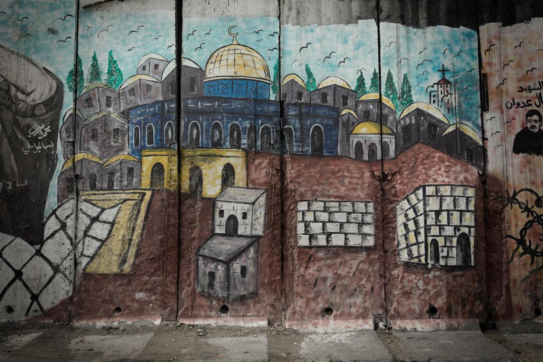 Een schildering van de Rotskoepel op de muur tussen het dorp Abu Dis en Jeruzalem. Vroeger kon je daar vanuit Abu Dis gemakkelijk naartoe lopen, maar door de muur is dat onmogelijk geworden.  Beeld Daniel Rosenthal