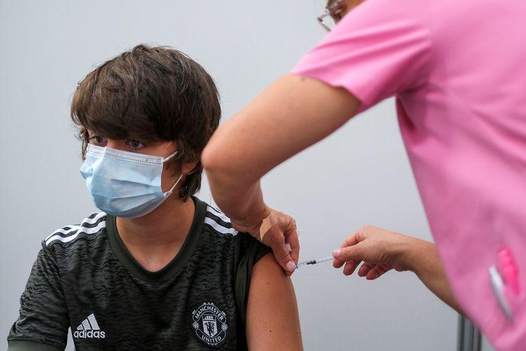 Een jonge Portugees wordt gevaccineerd. Beeld Reuters