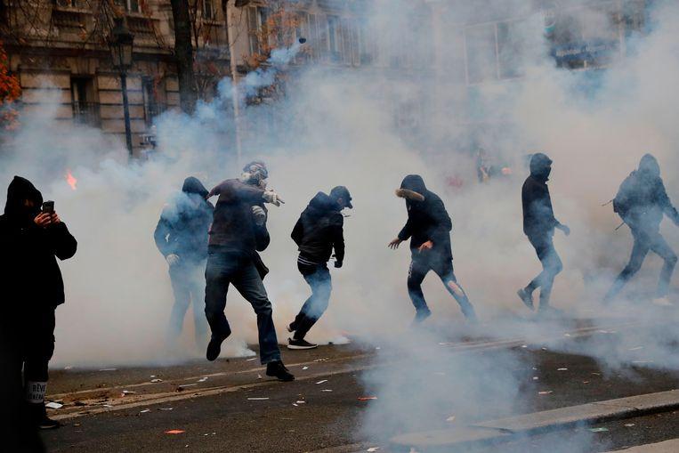 In het zwart geklede actievoerders veroorzaken rellen in Parijs. De politie zette traangas in. Beeld AFP