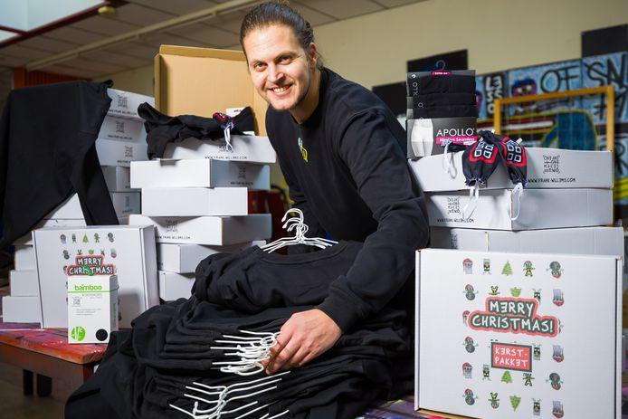 Kunstenaar Frank Willems met de kleding-kerstpakketten voor dak- en thuislozen.