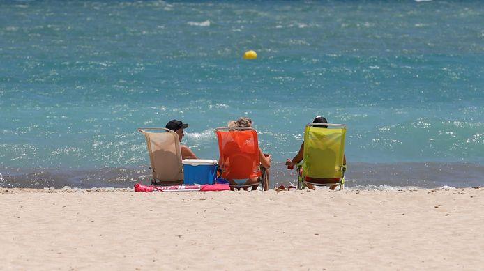 Zonnebadende toeristen bij het strand van Magaluf, in Palma de Mallorca, Spanje.