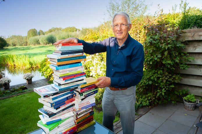 Gouwenaar Wim van den IJssel bij de enorme stapel boeken die hij heeft gelezen over kanker, gezondheid, voeding en leefstijl.