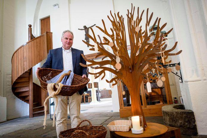 Dominee Dick Juijn met een voedselmand naast de wensboom in de toren van de Oude Blasiuskerk in Delden.