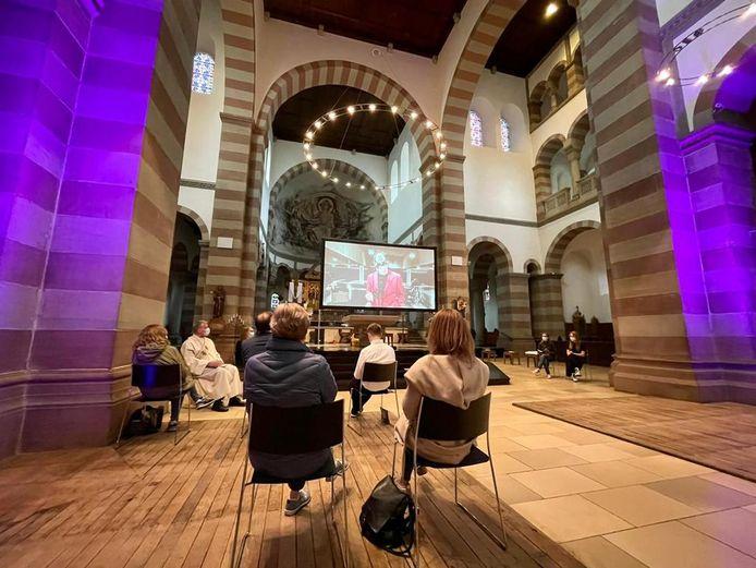 Homo-emancipatie, religie en pop komen samen in de Sankt-Antonius-Basilica in Rheine. Op het tv-scherm een videoclip van ENorm.