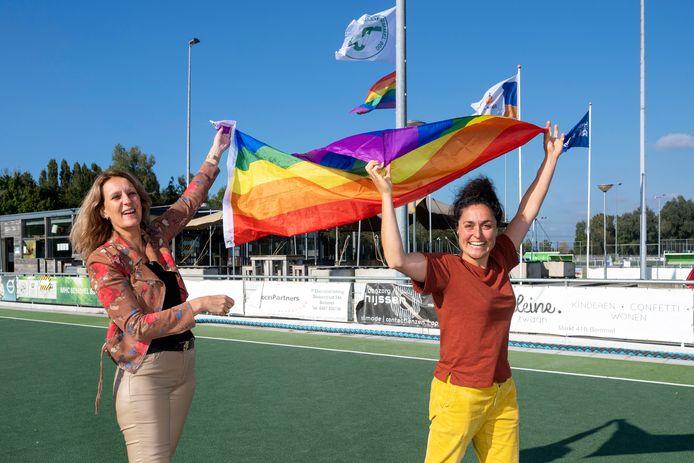 HC Bemmel-voorzitter Elsbeth van der Hoeven (links) hijst samen met Rosa Holtslag-Roelvink van de GSF de regenboogvlag.