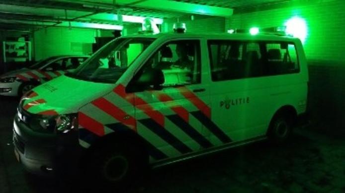 Politie rijdt met groen zwaailicht.