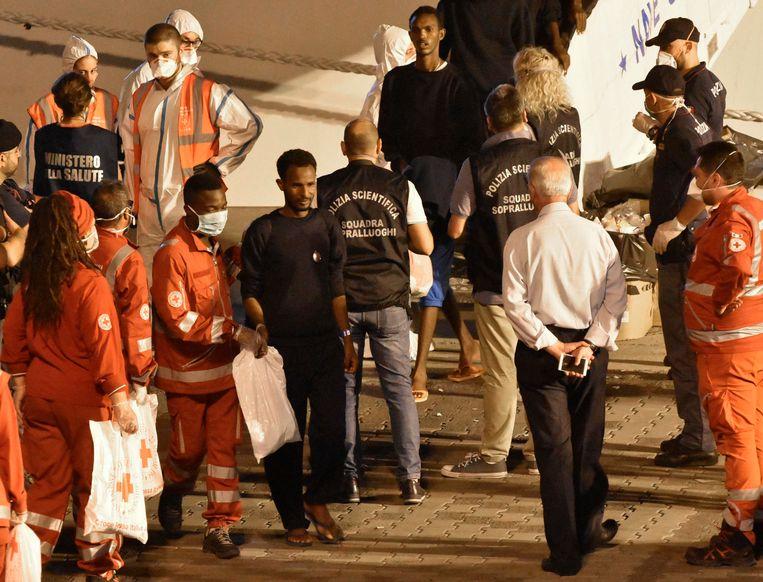 De migranten worden geïdentificeerd en ontvangen hulp tijdens het verlaten van de Diciotti zondagochtend.  Beeld AP