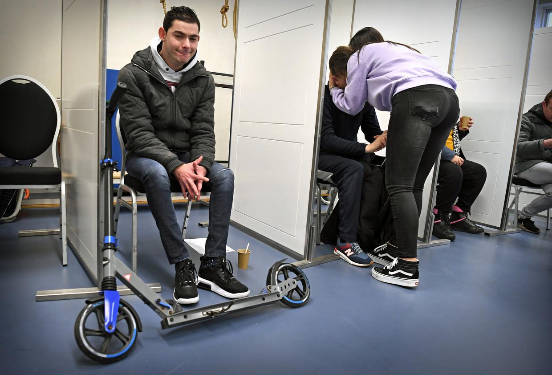 Bewoners van gehandicaptenzorginstelling Middin worden in Den Haag gevaccineerd met het coronavaccin. Na de prik komen ze een kwartiertje bij in een zaaltje waar ze koffie krijgen. Een cliënt wordt getroost door een begeleider.  Beeld Marcel van den Bergh / de Volkskrant