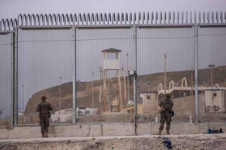 Spaanse soldaten bij een grenshek van de enclave Ceuta aan de noordkust van Marokko. Beeld AP