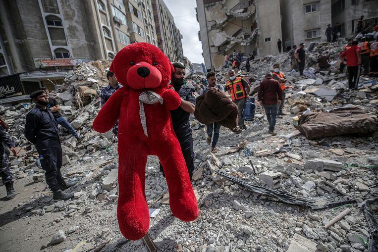 Een Palestijn trekt op zondag een rode teddybeer uit het puin na luchtaanvallen van het Israëlische leger op de Gazastrook. Beeld EPA