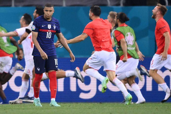 Kylian Mbappé baalt, op de achtergrond vieren de Zwitsers feest.